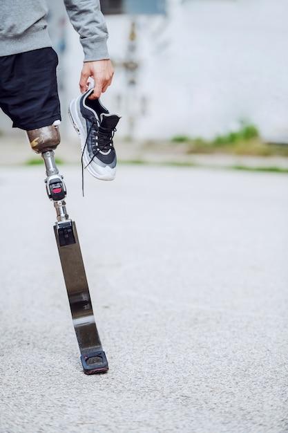 スニーカーを手に屋外で立っている白人の障害を持つスポーティな男の写真を切り取ります。 Premium写真