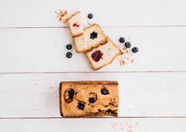 Cut pie with jam and blueberries on wooden table Free Photo