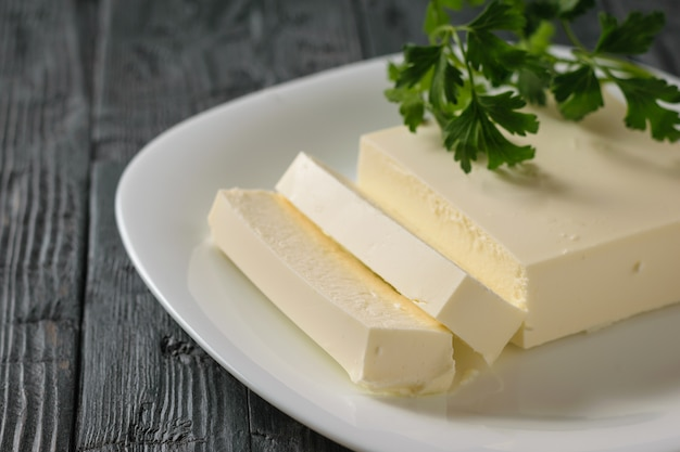 Cut serbian cheese with parsley leaves in a bowl on a wooden table. Premium Photo