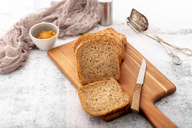 Cut slices of bread on wooden board with knife high view Free Photo