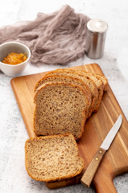 Cut slices of bread on wooden board with knife Free Photo