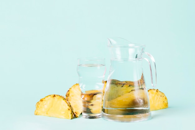 Cut slices of pineapple with water jug Free Photo
