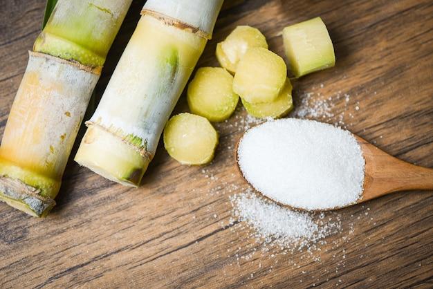 Cut sugar cane piece and white sugar on wooden spoon Premium Photo