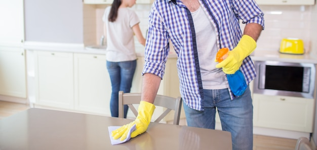 Cut view of man cleaning the surface of wood table. he wears yellow gloves. guy uses blue rag for cleaning. his wife is doing the same thing further forward. Premium Photo