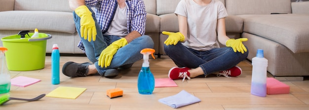Cut view of man and woman sitting on the floor and resting. she is meditating. man and woman has their legs crossed. there are cleaning equipment all over the floor. Premium Photo