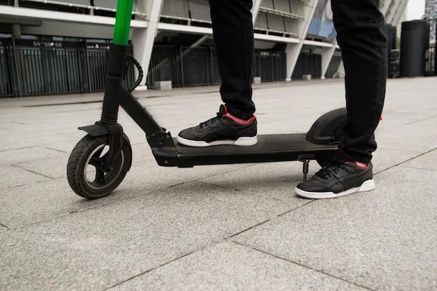 E-スクーターの上に立っている男性の足のカットビュー。大都市をドライブするスマートな方法。黒のスタイリッシュなスニーカー。男はスマホアプリで電動スクーターを借りた。エコ習慣。 Premium写真