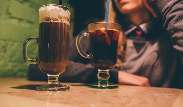 テーブルの上に座っている女性のカットビュー。ホイップクリームとグリューワインをグラスに入れたラテ。 Premium写真
