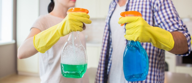 Cut view of two spay bottles. they are held by man and woman. girl holds green spray bottle while guy holds full blue one. people wear yellow gloves. Premium Photo