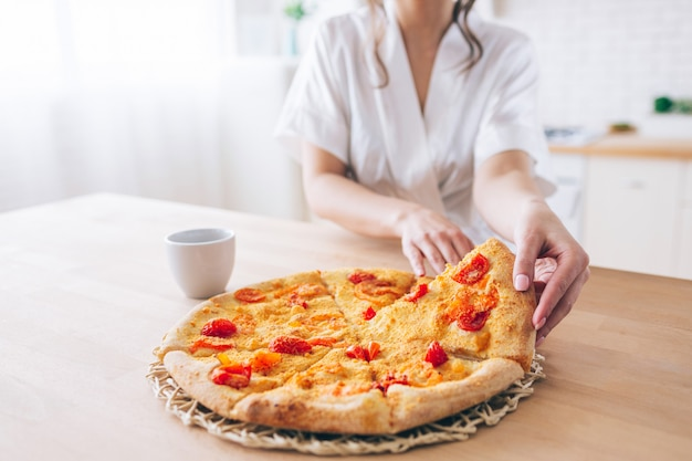 Cut view of woman in white dressing gown in kitchen. taking piece of pizza. small slice. young housekeeper live carefree life. Premium Photo