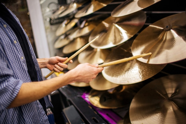 Cut view of young mantouching cymbals wit drum sticks. he stands alone in room. Premium Photo