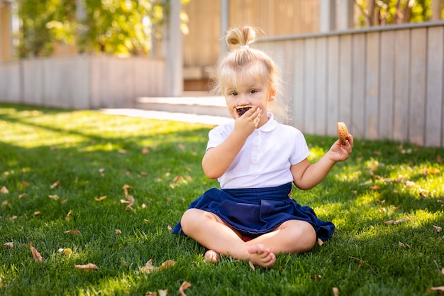 Cute adorable caucasian toddler baby girl sitting and eating Premium Photo