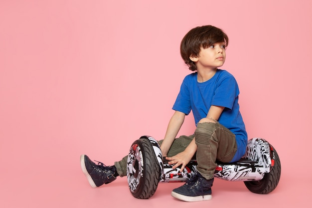 Cute adorable kid in blue t-shirt riding segway on pink wall Free Photo