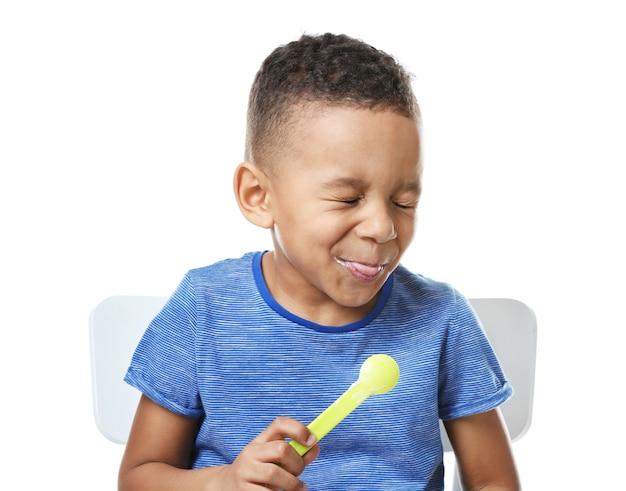 흰색 바탕에 요구르트를 먹는 귀여운 아프리카 계 미국인 소년 프리미엄 사진