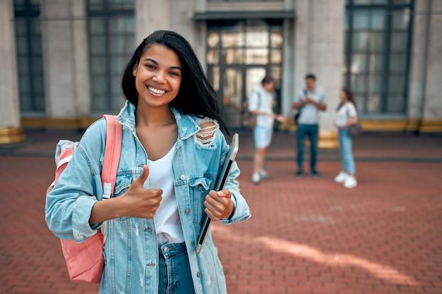 かわいいアフリカ系アメリカ人の女子学生がキャンパス近くのバックパックとラップトップでジェスチャーを親指を示しています Premium写真