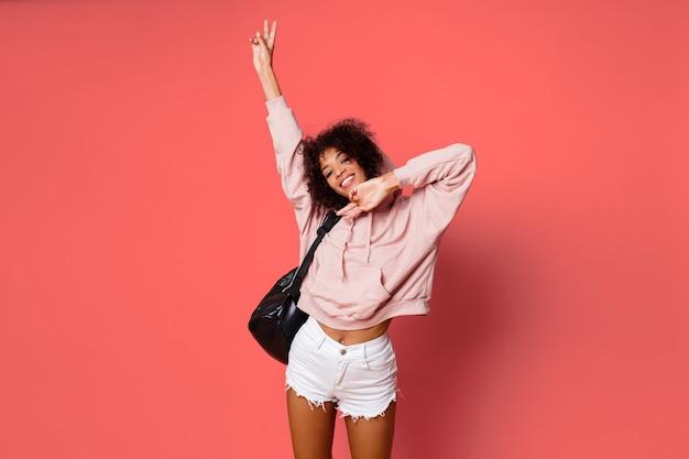 Cute african woman in pink sweatshirt making grimaces , having fun, posing over pink  background. Free Photo