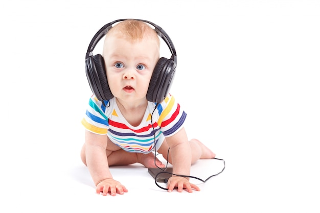 Cute amazed little boy in colorful shirt with headphones on head Premium Photo