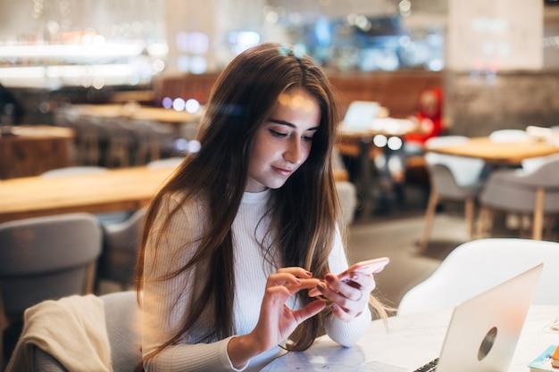 Милая и симпатичная молодая женщина на смартфоне в кафе Бесплатные Фотографии