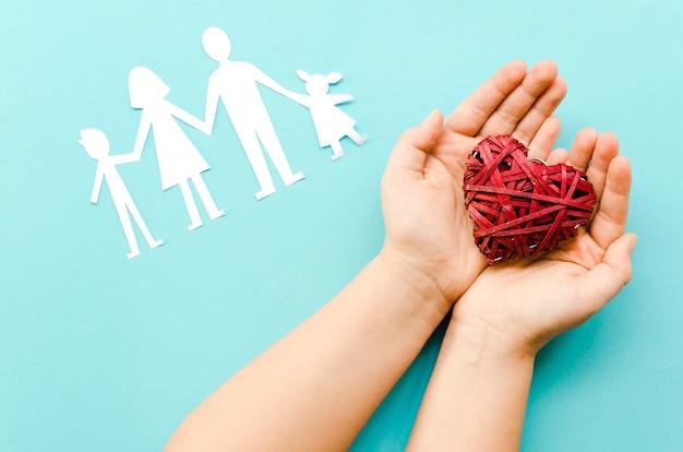 Симпатичная композиция из бумажной семьи на синем фоне с красным сердцем Premium Фотографии