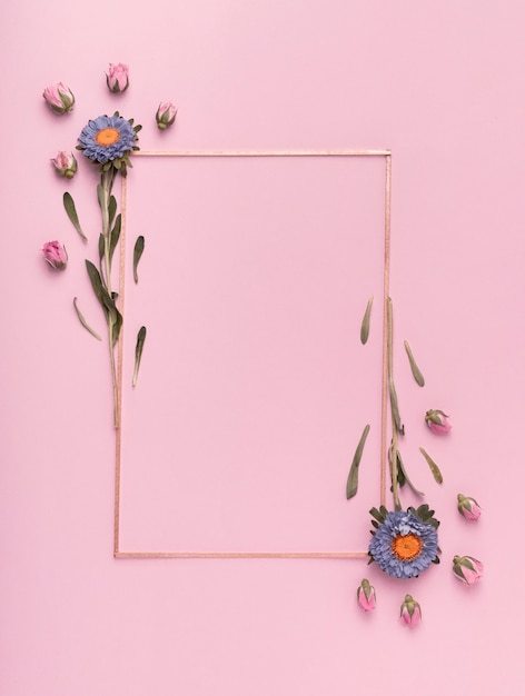 Cute arrangement of a vertical frame with flowers on pink background Premium Photo