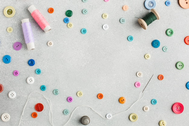 Cute arrangement with sewing threads and colourful buttons top view Free Photo