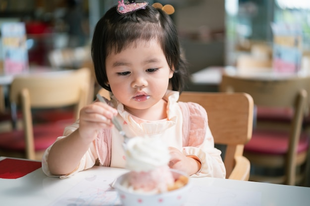 Cute asian baby eating ice-cream on the table in the restaurant Premium Photo