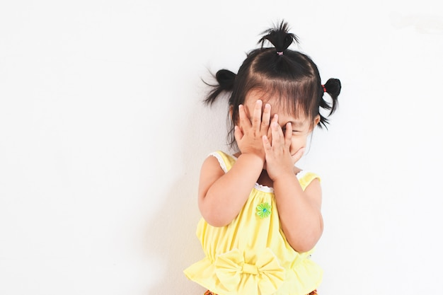 Cute asian baby girl closing her face and playing peekaboo or hide and seek with fun Premium Photo