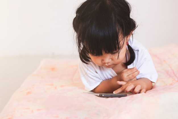 Cute asian baby girl playing smartphone lying on her bed in her room Premium Photo