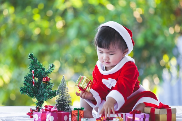 Cute asian baby girl wearing santa suit with beautiful gift boxes on christmas celebration Premium Photo