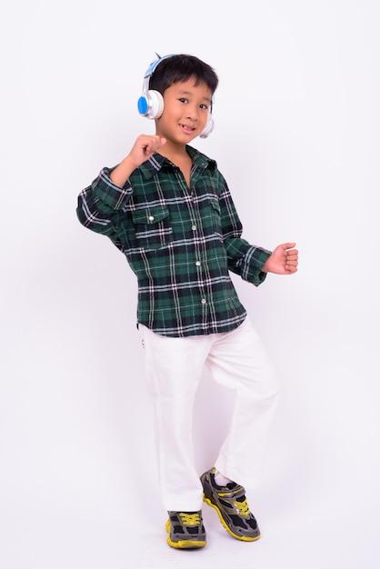 흰 벽에 녹색 체크 무늬 셔츠를 입고 귀여운 아시아 소년 프리미엄 사진