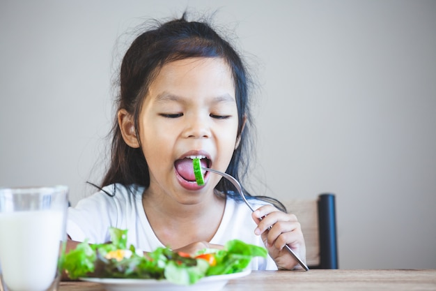 Cute asian child girl eating healthy vegetables and milk for her meal Premium Photo