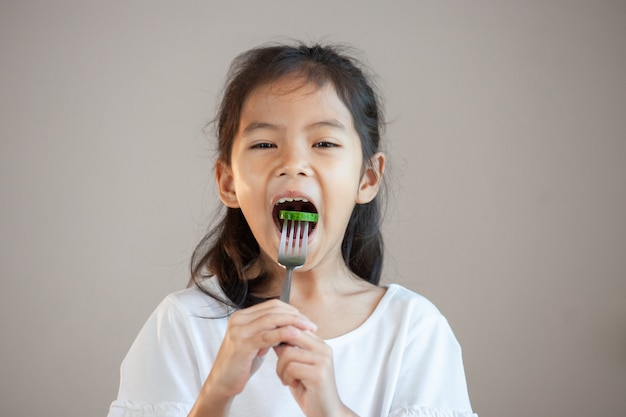 Cute asian child girl eating healthy vegetables with fork Premium Photo