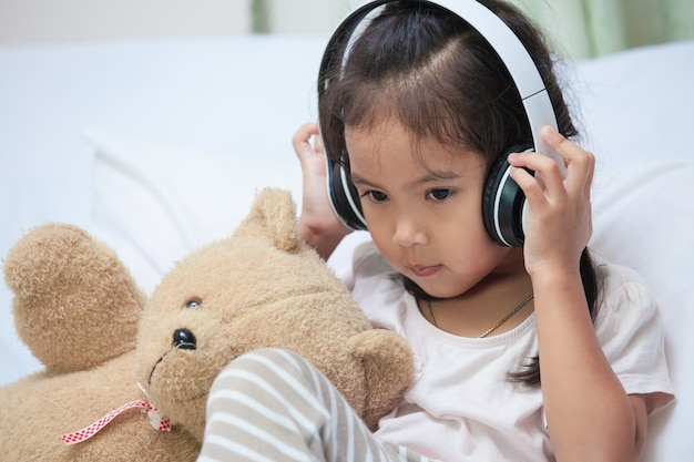 Cute asian child girl in headphones listening to music Premium Photo