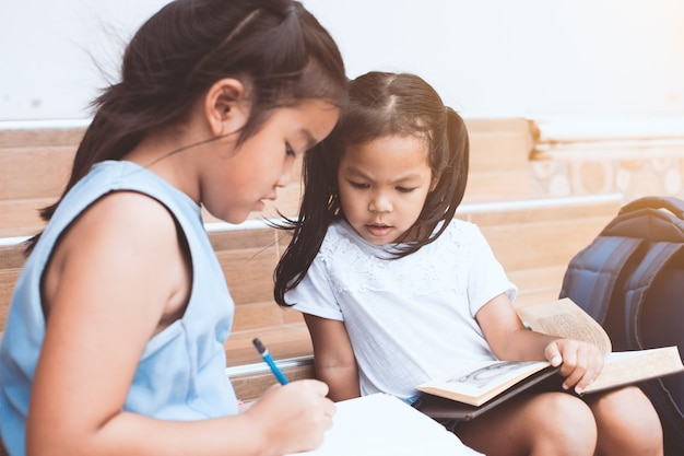 Cute asian child girl and her sister reading a book  together with fun and happiness Premium Photo