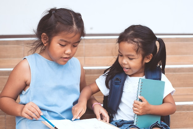 Cute asian child girl and her sister reading a book  together Premium Photo