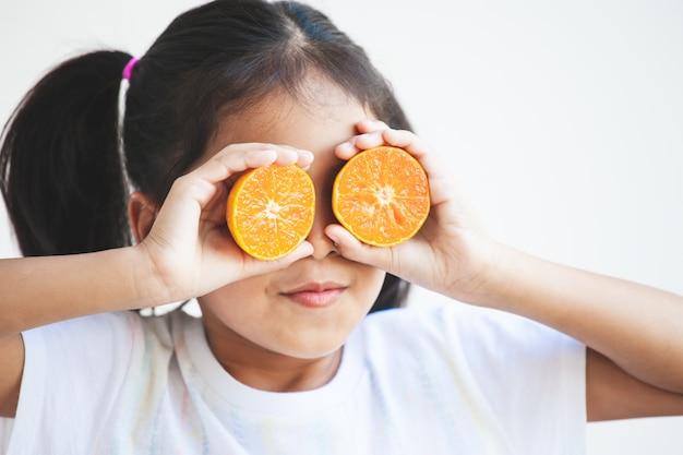 彼女の目を覆っている新鮮なオレンジを保持しているかわいいアジアの子女の子 Premium写真