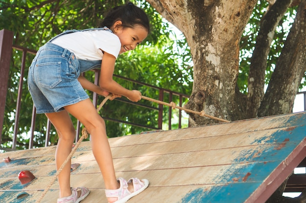 Cute asian child girl is climbing a wooden wall with a rope in the playground Premium Photo