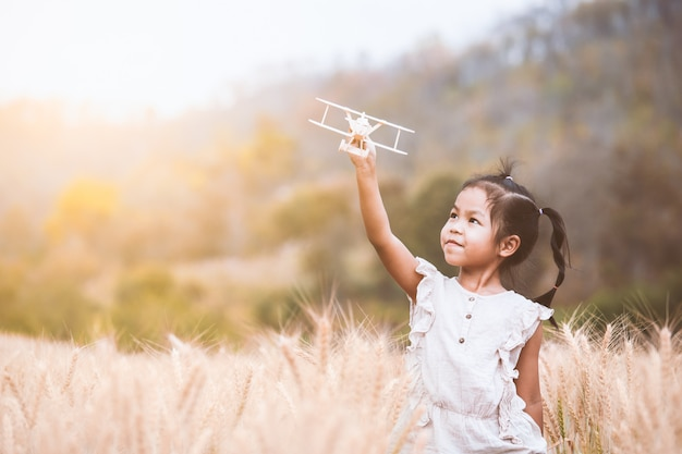 Cute asian child girl playing with toy wooden airplane in the barley field at sunset time Premium Photo