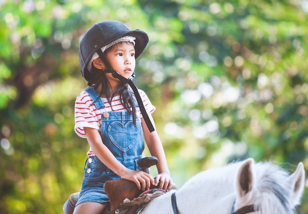 Cute asian child girl riding a horse in the farm with fun Premium Photo