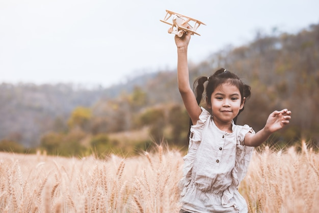 Cute asian child girl running and playing with toy wooden airplane in the barley field Premium Photo