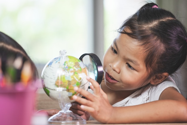 Cute asian child girl use magnifier to look and study at the globe in classroom Premium Photo