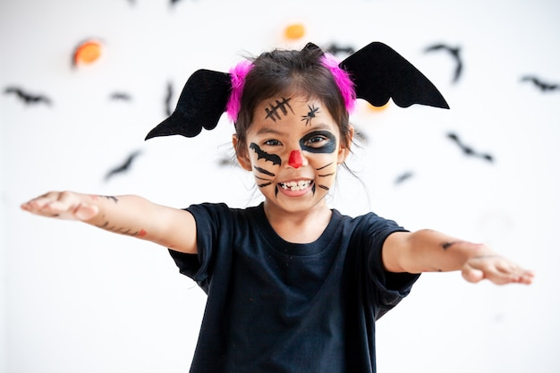 Cute asian child girl wearing halloween costumes and makeup having fun on halloween celebration Premium Photo