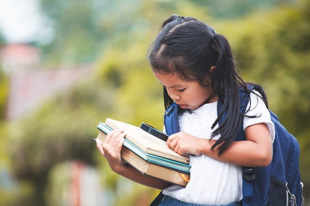 Cute asian child girl with school bag holding books and magnifying glass ready to go to sc Premium Photo