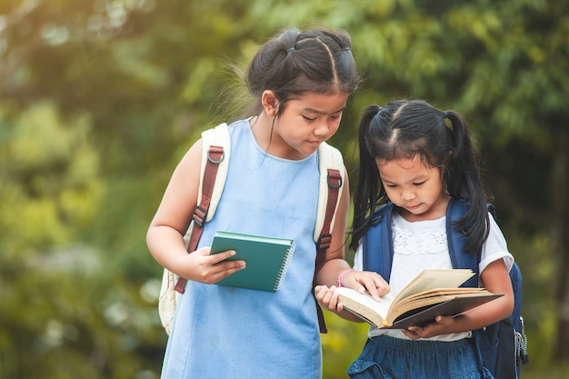 Cute asian child girl with school bag reading a book with her sister together Premium Photo