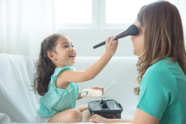Cute asian daughter putting makeup on her mother face at home. Premium Photo
