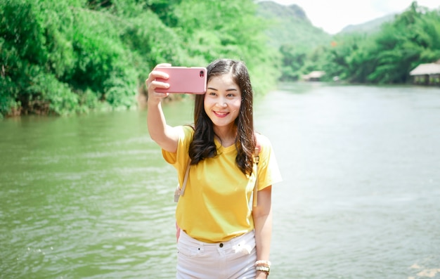 Cute asian girl, in a yellow t-shirt and a pink backpack, on her travel, she smiled take a selfie and posed in many moment with green nature place. Premium Photo
