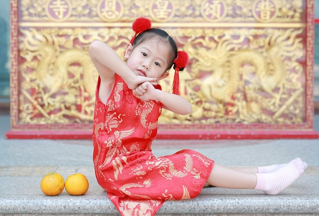 872cbd56e05d0 Cute asian kid girl in traditional chinese dress with gesture reverence  Premium Photo