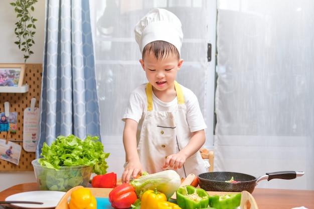 シェフの帽子とエプロンを楽しんで準備、キッチンで健康的な食品を調理しているかわいいアジアの小さな男の子の子供 Premium写真