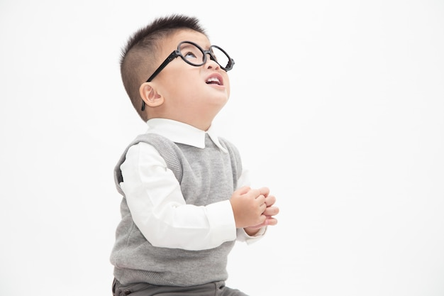Cute asian little boy wearing white shirt, grey vest and glasses isolated. creative ideas and innovation technology education concept Premium Photo