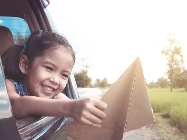 Cute asian little child girl having fun to play with toy paper airplane out of car window Premium Photo