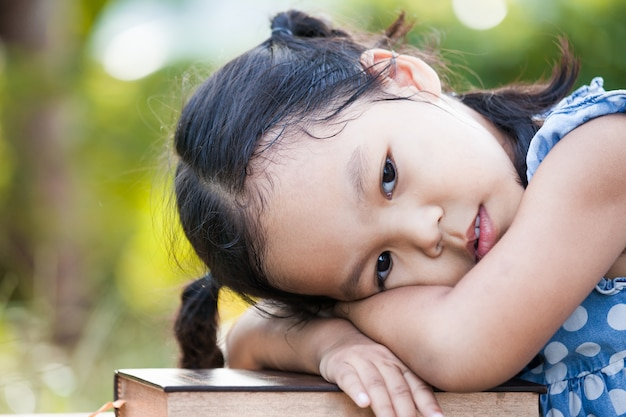 Cute Asian Little Child Girl With Bored Feeling To Read A